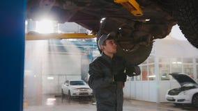 De garage automobiele dienst - een werktuigkundige onder bodem van auto controleert het wiel Royalty-vrije Stock Afbeeldingen