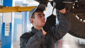 De garage automobiele dienst - een werktuigkundige onder bodem van auto controleert het wiel, omhoog sluit Stock Foto's