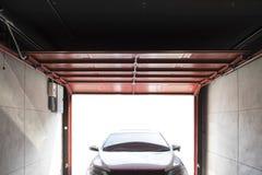 De garage opent de deur want de auto in garage wordt geparkeerd stock foto