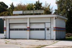 De garage van de autodienst door eigenaars na het uitgaan van zaken met gebroken neontekens wordt verlaten op hoogste en dilapida royalty-vrije stock afbeelding