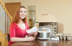 De garantiekaart van de vrouwenlezing voor nieuw langzaam kooktoestel Stock Fotografie
