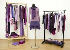 De garderobe met purpere kleren schikte op hangers en een uitrusting op een ledenpop stock foto's