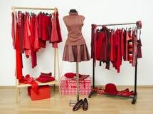 De garderobe met rode kleren schikte op hangers en een uitrusting op een ledenpop royalty-vrije stock fotografie