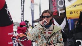 De gastheer met microfoon zegt woorden De skiërs en snowboarders kamperen binnen bij de skitoevlucht stock footage
