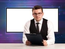 De gastheer van het televisieprogramma met het grote exemplaarscherm in zijn rug royalty-vrije stock afbeeldingen