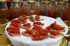 De gastronomische minibeten van gespeld brood met pesto van basilicum en olijven en tuintomaten op een wit plateren op een landbo royalty-vrije stock afbeeldingen