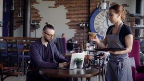 De gastvrije jonge serveerster bij de koffie brengt glas koffie aan cliënt De jonge modieuze mens in vrijetijdskleding is stock video
