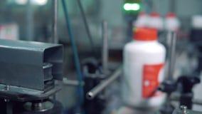 De geëtiketteerde plastic flessen bewegen zich en rollen in dichte omhooggaand stock videobeelden