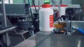 De geëtiketteerde plastic flessen bewegen zich langs de transportband en worden duidelijk stock footage