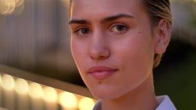 De geïnspireerde jonge moderne vrouw let op bij camera in avond, glimlachend, vertroebelde lichten op achtergrond stock video