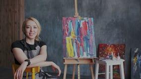 De geïnspireerde mooie zitting van de blonde vrouwelijke kunstenaar in haar werkplaats Zij glimlacht en onderzoekend de camera mo stock footage