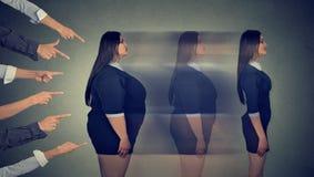 De geïntimideerde zwaarlijvige vrouw zet haar lichaam door strikt dieet om stock foto