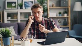 De geïrriteerde kerel freelance arbeider spreekt op mobiele telefoon en gebruikt laptop uitdrukkend negatieve emoties binnen werk stock footage