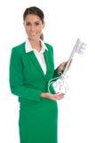 De geïsoleerde bedrijfsvrouw in groene holdingssleutel voor wijdt een hous Royalty-vrije Stock Fotografie