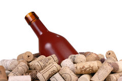 De geïsoleerde fles van de wijn en heel wat wijn-wine-corks Stock Afbeeldingen