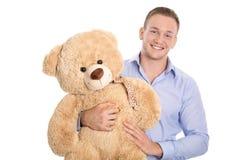 De geïsoleerde glimlachende gelukkige teddybeer van de jonge mensenholding in zijn handen Stock Afbeelding