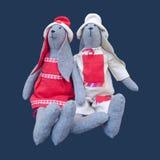 De geïsoleerde met de hand gemaakte familie van het poppenkonijntje in homespun kledingssittin Stock Afbeelding