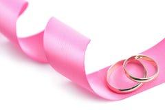 De geïsoleerde) ringen van de gouden bruiloft over roze lint Royalty-vrije Stock Foto's