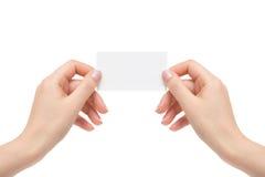 De geïsoleerde vrouwelijke handen houden witte kaart op een witte achtergrond Royalty-vrije Stock Foto's
