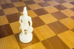 De geïsoleerde witte schaakbischop van steen op de vierkante houten raad Stock Afbeeldingen
