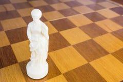 De geïsoleerde witte schaakkoningin van steen op de vierkante houten raad Stock Afbeelding