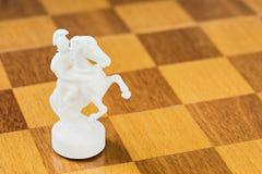 De geïsoleerde witte schaakridder van steen of plastiek op de vierkante houten raad Stock Afbeeldingen