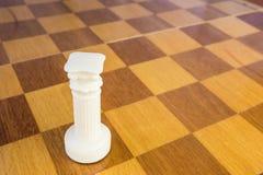 De geïsoleerde witte schaakroek van steen op de vierkante houten raad Stock Foto's