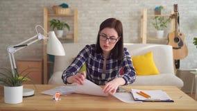 De gealarmeerde jonge vrouw maakt een berekening gebruikend een calculatorzitting bij een lijst stock videobeelden
