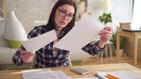 De gealarmeerde verraste jonge vrouw maakt een berekening gebruikend een calculatorzitting bij een lijst stock footage
