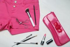 De geassorteerde reeks van maakt omhoog hulpmiddelen op roze jeans Royalty-vrije Stock Afbeeldingen
