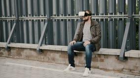 De gebaarde aantrekkelijke mens gebruikt virtuele werkelijkheidsglazen op het dak, stijgt zijn glazen op en gaat weg 4K Stock Fotografie