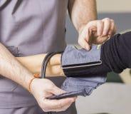 De gebaarde arts die glazen dragen controleert de de bloeddruk en impuls van de patiënt stock afbeelding