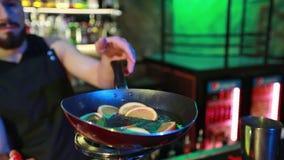 De gebaarde barman bereidt een cocktail op een ronde gasring in voor een nachtbar stock video