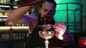 De gebaarde barman giet voorbereide cocktail in een glas stock video