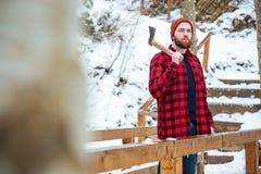 De gebaarde bijl van de mensenholding en het denken in de winterbos Stock Afbeeldingen