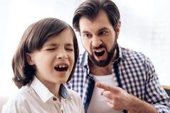 De gebaarde boze vader berispt schreeuwende zoon stock afbeelding