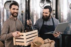 De gebaarde brouwer in schort met laptop neemt fles van doos, die door de vrolijke mens wordt gehouden royalty-vrije stock afbeelding