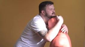 De gebaarde en vermoeide Kaukasische mens omhelst model voor het in dozen doen na opleiding stock videobeelden