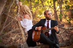 De gebaarde gitarist en het meisje zitten op boomtak Stock Foto's