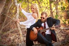 De gebaarde gitarist en het meisje zitten op boomtak Stock Foto