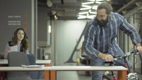 De gebaarde glimlachende mens berijdt zijn fiets in het moderne bureau De ruiter zegt hello aan zijn vrouwelijke collega en zit b stock videobeelden