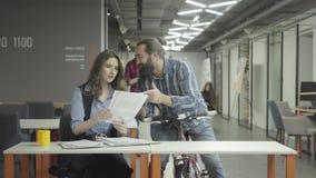 De gebaarde glimlachende positieve mens berijdt dichter zijn fiets met in hand documenten en toont documenten aan de dame in het  stock video