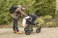 De gebaarde glimlachende vader met een rugzak en in gele laarzen die met een kinderwagen in een de lentepark lopen toont zorg en  stock foto