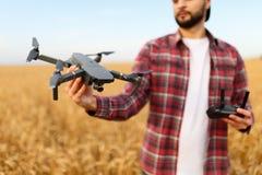 De gebaarde hipstermens toont kleine compacte hommel en houdt ver controlemechanisme in zijn hand De landbouwersagronoom bekijkt royalty-vrije stock fotografie