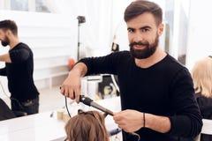 De gebaarde kapper maakt krullen op haar van mooi meisje met haarkrulspeld stock afbeeldingen