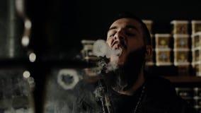 De gebaarde kerel dichte omhoog rokende waterpijp en maakt ringen van rook in langzame motie stock videobeelden