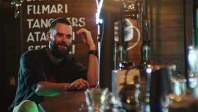 De gebaarde kerel drinkt een cocktail en communiceert met de barman bij de barteller in 4k resolutie in langzame motie stock video