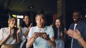De gebaarde kerel met expressief gezicht maakt wens en blaast kaarsen op verjaardagscake terwijl zijn collega's slaan stock video