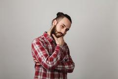 De gebaarde knappe mens denkt in rood geregeld overhemd op grijze bedelaars Royalty-vrije Stock Foto