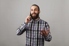 De gebaarde knappe mens spreekt telefonisch in blauw geregeld overhemd o royalty-vrije stock fotografie